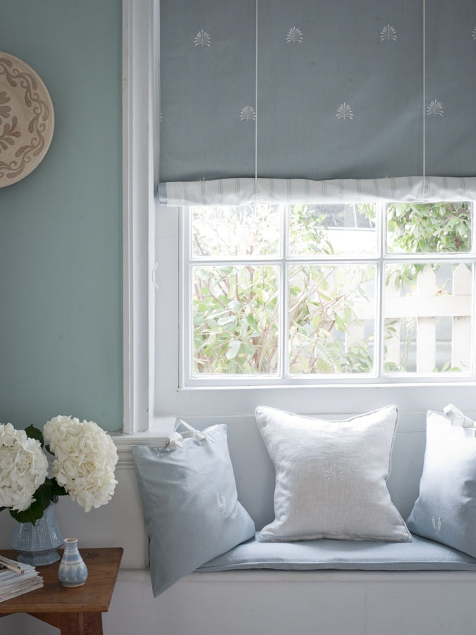 Swedish blind in Cloudy Blue linen with white embroidered frond motif, and reverse fabric in cloudy blue linen stripe from Moghuls Signature range. Scatter cushions in blue and white linen stripe and check from the same range with piped or ruffle edges.