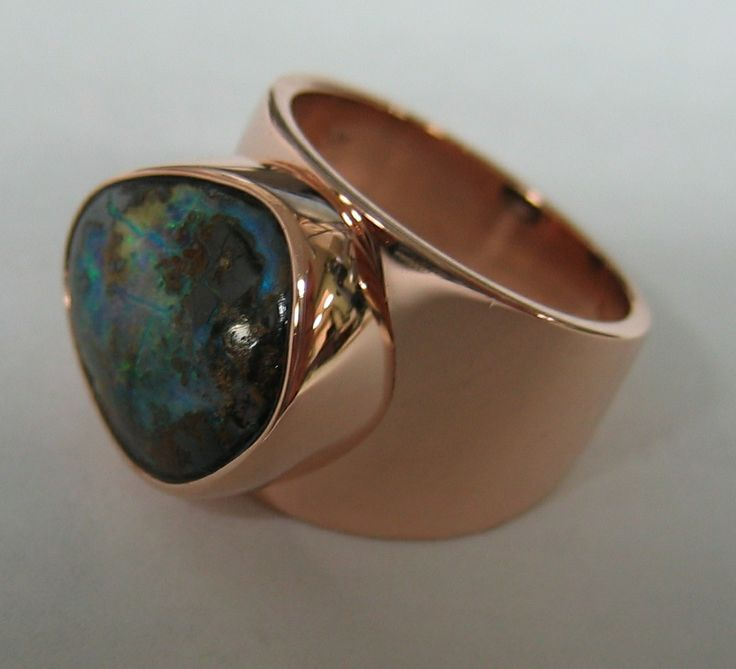Custom designed fashion ring by Designs In Gems containing a bezel set boulder opal set in an 18kt yellow/rose gold mounting.