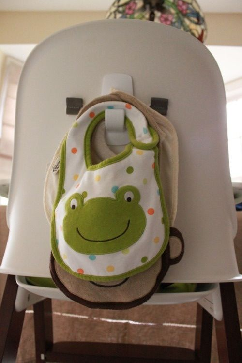 Put command strips on the back of a high chair for bibs to hang on!