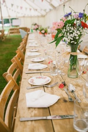 Countryside wedding theme. Long tables, no table cloth and a simple decor makes this rather beautiful.