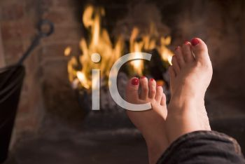 Royalty Free Photo of a Woman's Feet Warming at a Fire