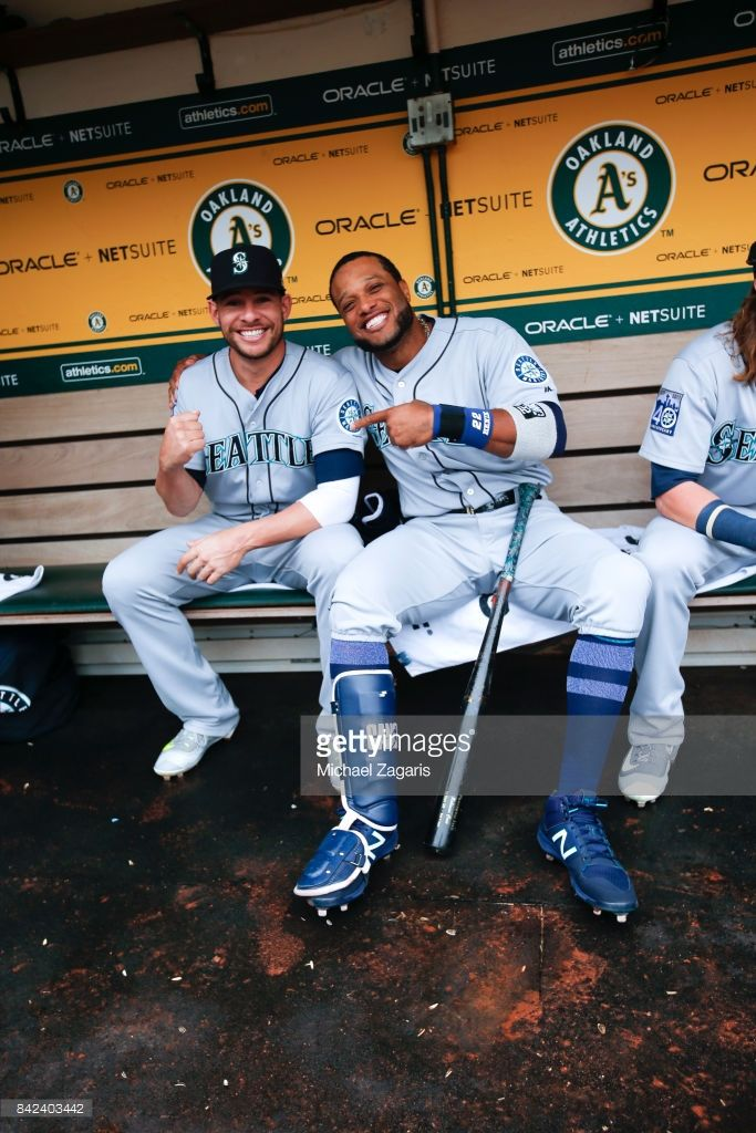 Danny Valencia #26 and Robinson Cano #22 of the Seattle Mariners sit in the dugout prior to the game against the Oakland Athletics at the Oakland Alameda Coliseum on August 9, 2017 in Oakland, California. The Mariners defeated the Athletics 6-3.
