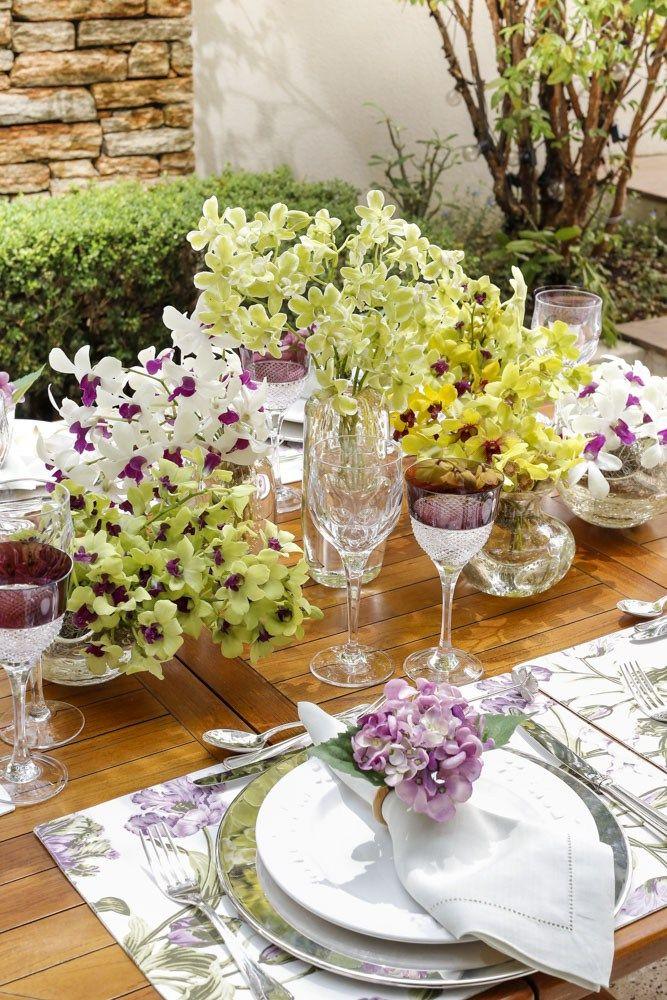 Para aumentar a sensação de se estar em um jardim, apostamos em trêstipos de flores que adoramos, orquídea, tulipa e hortênsia. Aprimeira floriuosvasosno centro da mesa,a segunda estava representada na estampa floral dos jogos americanos da nossa marca Couvert, e a terceira nos porta-guardanapos também daCouvert.