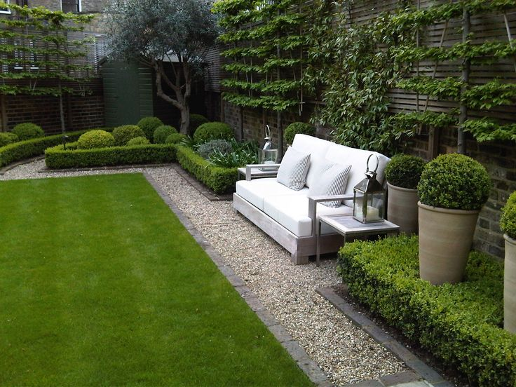 lush green grass, grey brick edging around garden beds, box hedges & espalier trees on panelled privacy screens. Peacefull