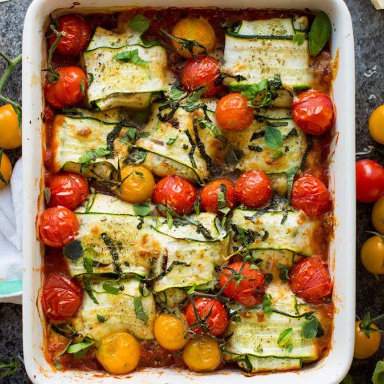 Veggie filled zucchini ravioli stuffed with ricotta and baked over a simple marinara sauce with burst cherry tomatoes. Gluten Free