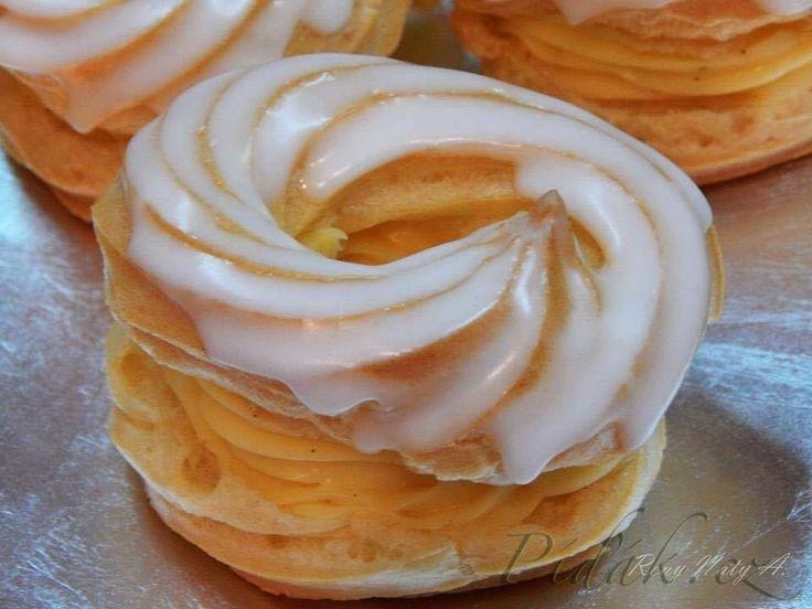 POTŘEBNÉ PŘÍSADY:  250ml vody 90g másla špetka soli  140g hl. mouky 3 vejce  Krém: 0,5l mléka  2 vanilkové pudinky  100 g cukru  150g másla  1 vanilkový lusk  2PL rumu  Poleva: 1 bílek 1-2 pol.