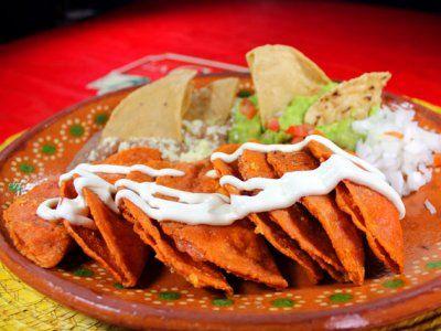 Receta de Enchiladas Potosinas Mexicanas | Las Enchiladas Potosinas llevan una masa preparada con chile rojo que les da su color. Estas van rellenas de una mezcla de queso fresco con chile y cebollita. Se sirven con crema fresca, lechuga en tiras y guacamole.