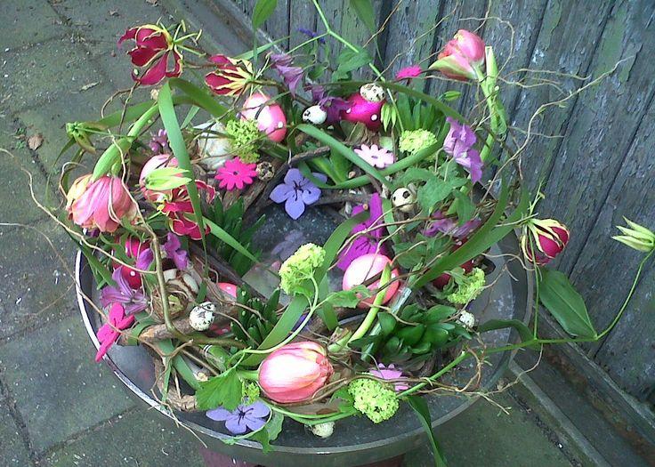 Vrolijke paaskrans, gemaakt  met o.a  Franse tulp, Clematis, Gloriosa, Viburnum.