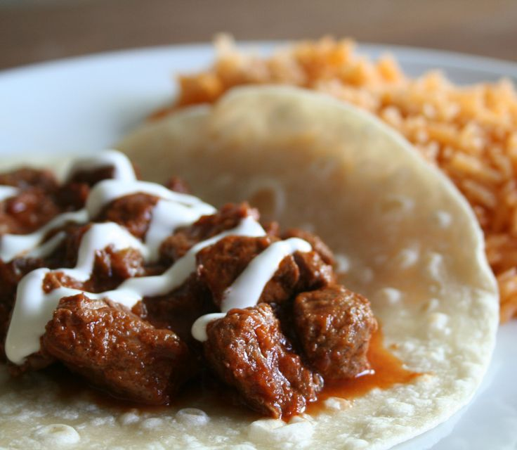Slow Cooker Steak Burritos, served on homemade style tortillas, and spanish rice on the side!