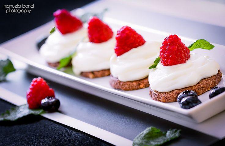 Mini cheesecake con lamponi e mirtilli su biscotto integrale al cacao. Food photography