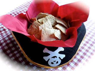 Looking for pirate party food ideas? Use ordinary food served in extra-ordinary pirate hats. Turn it upside down, place a red napkin inside it and use it to serve chips or your favorite snack.