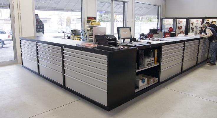 Bancone-reception scelto per l'arredamento del negozio di utensileria Pro Store, a Padova. Si tratta della composizione di armadi industriali Fami Storage Systems, serie Standard e Perform assemblati ed uniti da un piano in MDF rivestito in gomma.