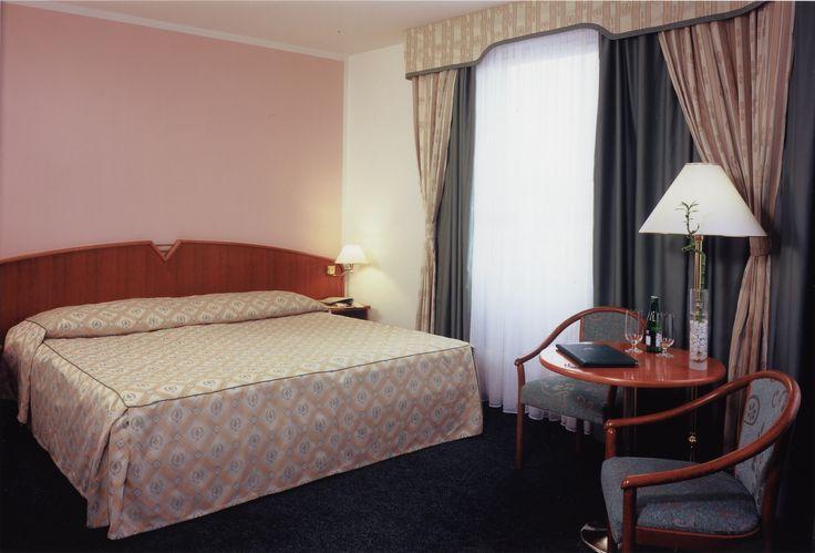Hotelový pokoj s okenními dekoracemi čalouněním a přehoz přes postel z Ateliéru Orsei #závěs #zelená #hotel #přehozpřespostel #čalounění