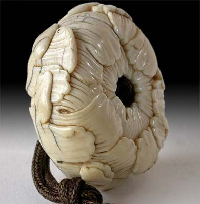Side view of antique Japanese Netsuke of a chrysanthemum flower.  (A carved…