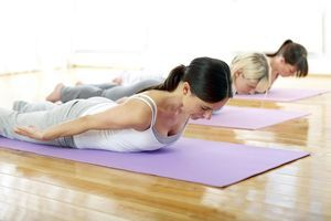 Germany, Hamburg, Yoga instructor and female trainee doing yoga exercise in gym room