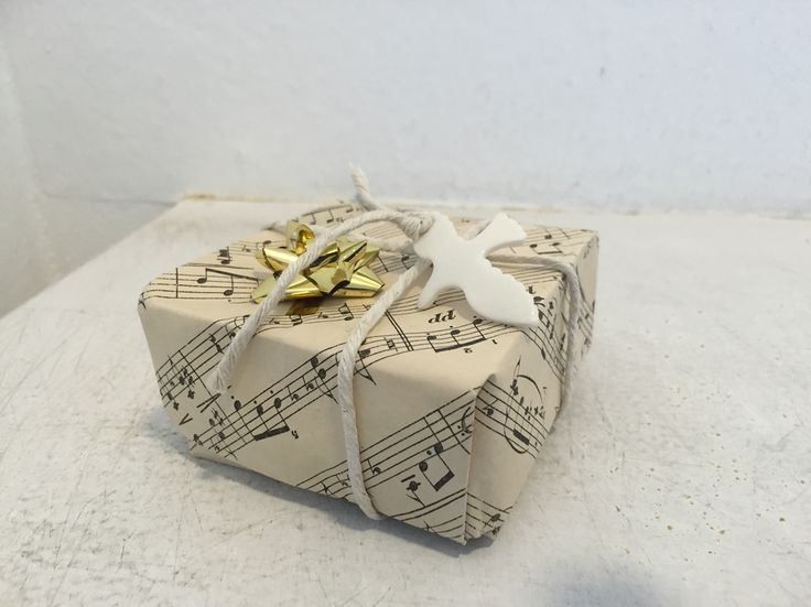 Coffee stained music notation printed paper folded into a box decorated with a ceramic bird