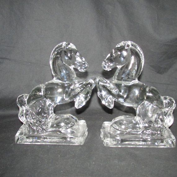 These sculptured, glass, rearing horses by Fostoria are hollow on the inside because they were candy filled at one time. The horses would have had a cardboard bottom. These horses measures 5 1/2 inches long and stands about 7 1/2 inches. Together, they weigh almost 6 pounds. This pair has the ridged mane. #2564  NOTE: We have a second pair of horse bookends with the beaded mane. Same size and weight. #2580 The last pictures shows beaded mane horse.  You will see other have the same ...