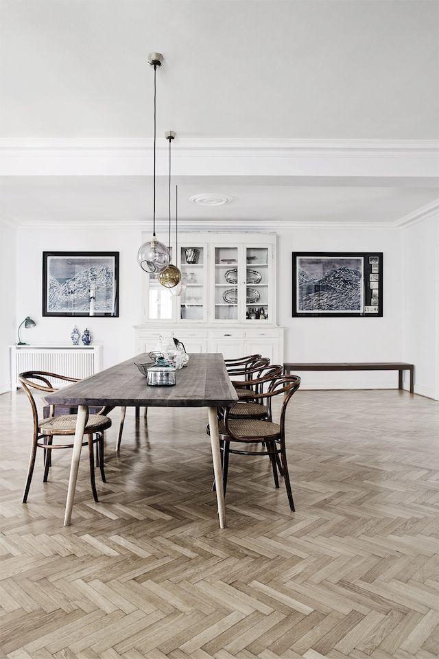 wooden table, herringbone floor and low hanging pendant lights