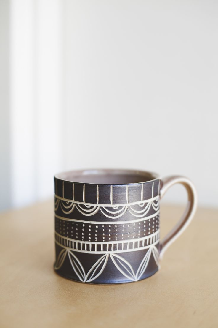 "Bold and grounded this mug is a celebration of cultural ornamentation. It has a mauve color shiny glaze on the interior and a raw black hand carved exterior. Approx 3.5"" tall."