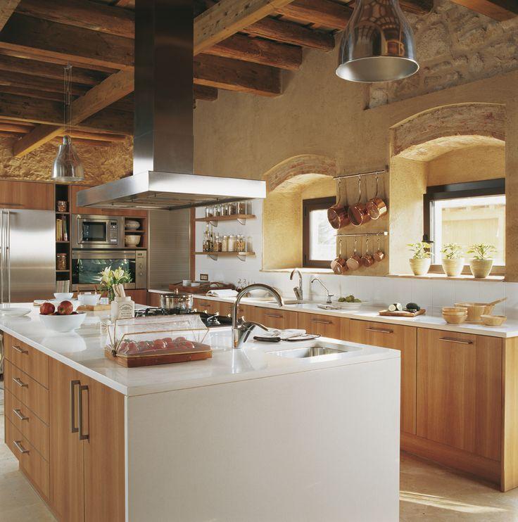 cocina con una gran isla central con muebles de madera paredes de piedra y vigas
