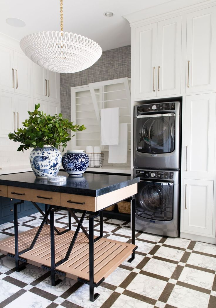 Drying racks, double washer and dryer, laundry room island - this space is fully loaded and a mom's dream come true! Designed by Alice Lane Home Photo by Nicole Gerulat
