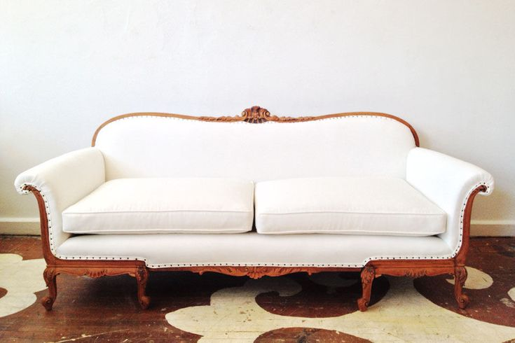 We redid this beautiful antique sofa for our showroom. We knew it was a diamond in the rough in its former state (it still had the original burgundy upholstery and horsehair stuffing) but even we were surprised by how lovely and fresh the sofa looked when sanded and upholstered in a white linen.