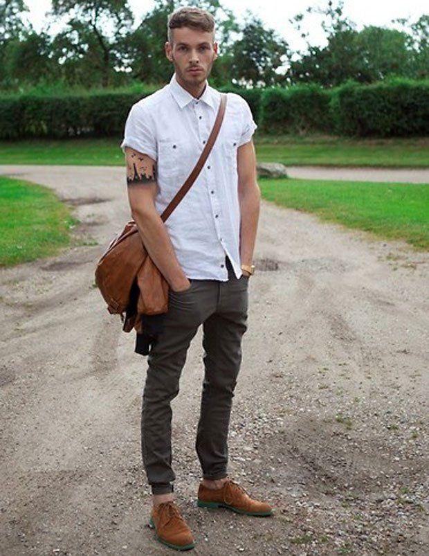 Look com camisa branca, calça chino marrom e sapato marrom. Detalhe para a bolsa de couro masculina.