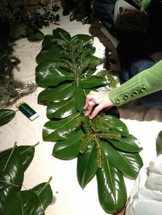 stapling magnolia leaves and bows to piece of wood for some christmas swag