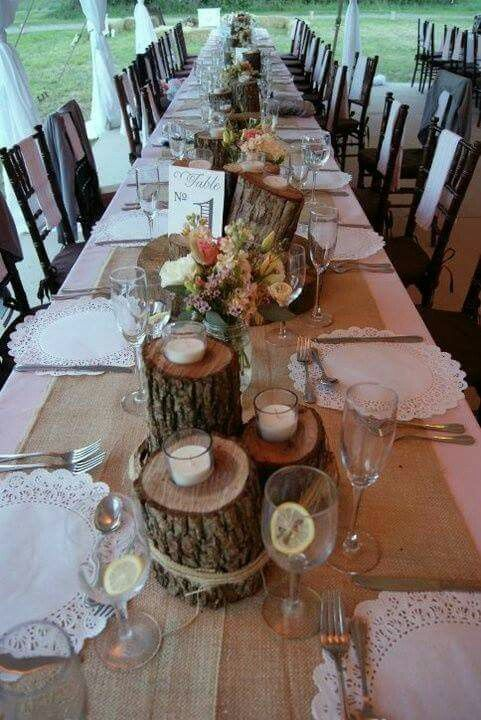 I adore these centerpieces. Different size logs with candle holders drilled on top wrapped with twine. Could add table numbers on slice of wood