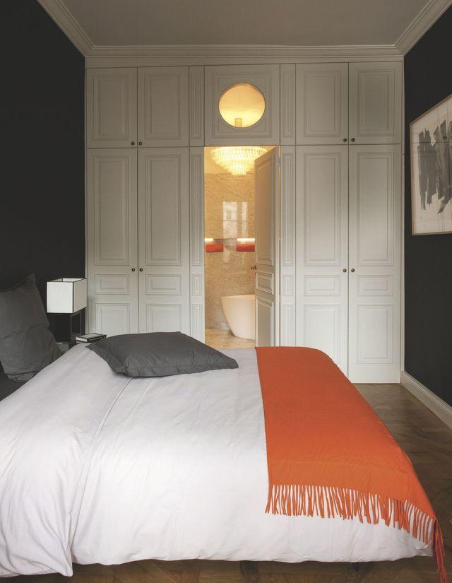 """Dans la chambre, un plaid orange vitaminé Brun de Vian-Tiran vient rehausser le gris du linge de lit. Au fond, des placards réalisés sur mesure s'ouvrent sur la salle de bains, imperceptible lorsque la porte est fermée. Précieuse, cette pièce est recouverte d'un marbre de Carrare. Baignoire îlot """"Stori"""" (Leroy Merlin) choisie pour sa petite taille et ses lignes contemporaines. Lustre en verre de Murano."""