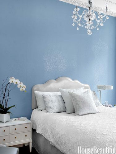The Wolf Home headboard, hung on the wall to save space, is upholstered in a silver fabric from Gray Line Linen.