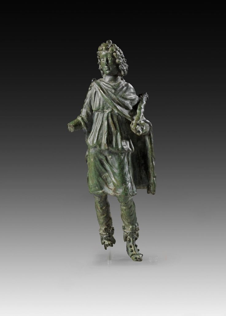 ´Dendrophoros´. Bronze figurine of a long-haired young man wearing trousers, a knee-long tunic and a mantle of the same lenght. Roman Imperial Period, 2nd century A.D. Green patina, right hand and right foot broken. In der angewinkelten Rechten liegt ein sprießendes Baumstämmchen. Dendrophoros=1) An epithet of Sylvanus 2) A college of priests who carried about branches of trees in procession, in honor of a divinity.