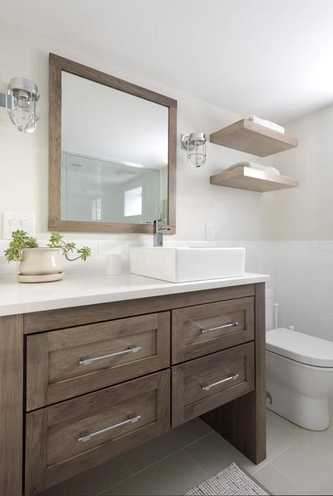 Fantastic bathroom features a walnut stained vanity with 4 drawers topped with a rectangular overmount vessel sink and modern faucet placed under a walnut stained mirror lit by cage wall sconces.