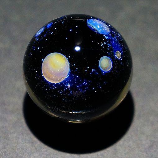 土星のような環・輪のある惑星がガラスの中で浮いています。 裏側は二次元の宇宙が描かれています。  Glass marble wa Size 29mm