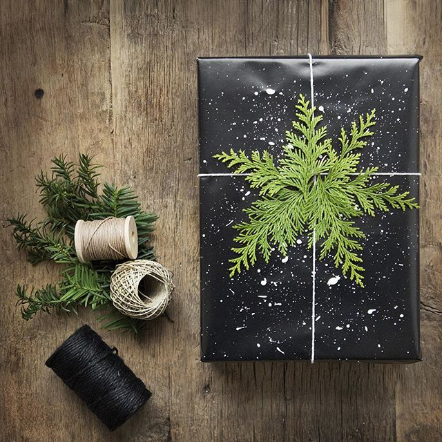 black wrapping paper w/ white paint splatter (snow) & evergreen (snowflake):