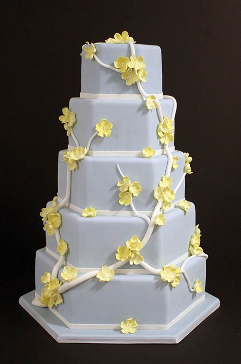 White branches and yellow sugar flowers embellish a baby blue hexagonal cake.
