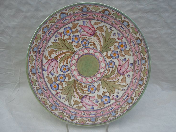 A 1940s HJ Wood Bursleyware large wall plaque, designed by Charlotte Rhead in the TL76 Wind Tossed Tulips pattern, having a tube-lined decoration of flowers and leaves enamelled and lustred in various colours, on an mottled grey ground, printed marks verso, 41.5cm diameter