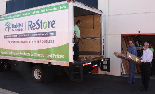 Dave Hall, CEO, 3 Day Blinds, and Frank Gutierrez, VP, Manufacturing & Supply Chain, 3 Day Blinds, help load boxes into the Habitat for Humanity Truck.