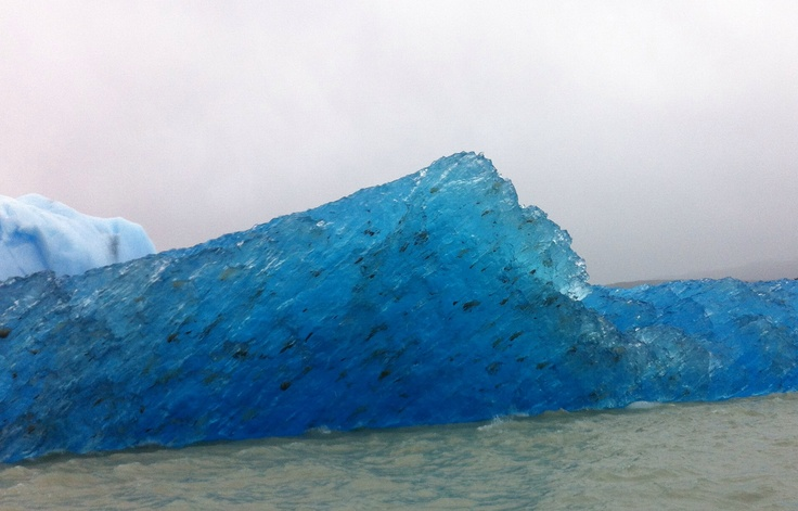 The blue colour is correct. Note the rocks embedded in the iceberg.