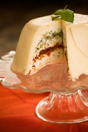 Layers are pesto, sun-dried tomatoes, cream cheese mixture w/ pistachios, covered with provolone