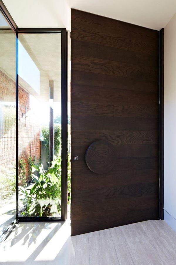 Porta de madeira escura e puxador redondo.
