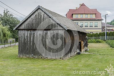 Small shed with school building in the background in small village Roznow, POland.Europe