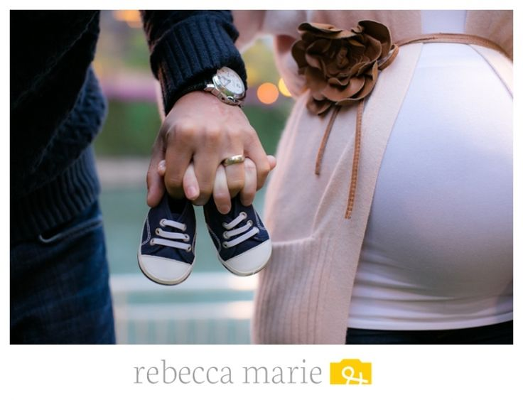 Maternity photo showing a pair of shoes to indicate if the baby is a boy or girl...cute!