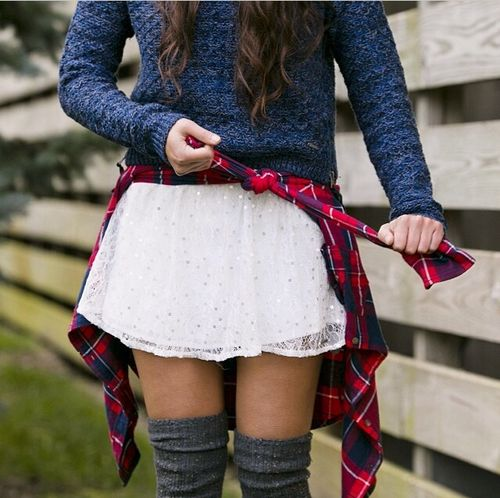 White skirt, dark sweatshirt, and thigh high socks served on a platter.: