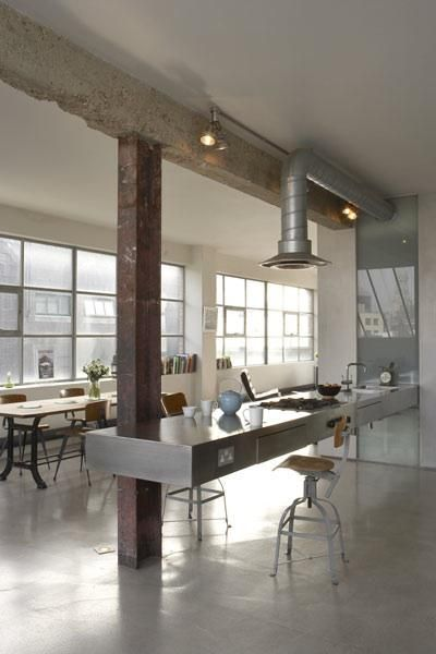 The London loft of Ochre partner Solange de la Fouchardière features polished concrete floors, exposed ventilation ducts, and a glass backsplash.