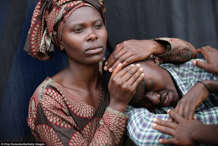 A woman consoles Bizimana Emmanuel, 22, during the 20th anniversary commemoration of the 1...