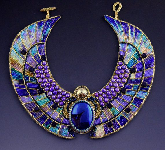 Feminine high fashion collar necklace in angelic color palette of violet, lavender, turquoise, blue, and gold. There is so much light, depth, and movement that camera can not capture.  Inspired by ancient Egyptian mythology and art, it combines Art Deco style geometrical shapes with ancient mythological scarab motif, resulting in a decadent, opulent, mosaic like jewelry treat. Little bead embroidered squares radiate out from the scarabs body, and each square is different, full of dimension…