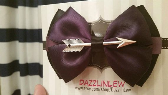 The wonderful Hawkeye complete with an arrow symbolizing his great skills. Made of a deep plum purple satin ribbon and topped with a silver arrow