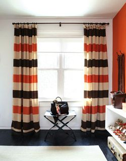 striped curtains & love the shoe shelf display to the right    love the color in the curtains and the statement wall (wouldn't do orange)