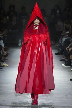 "Rei Kawakubo presented a bouquet of ""roses and blood"" tonight at Comme des Garçons. That is how she described the intense and disturbingly allusive immersion in the color red that she sent out in the raw surroundings of a derelict warehouse for spring 2015."